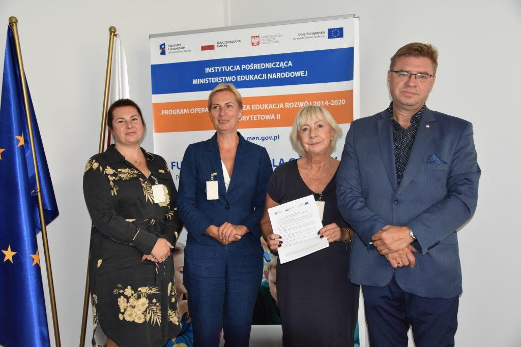 Podpisanie umowy. Na zdjęciu stoją  trzy przedstawicielki firmy Eduexpert Sp. z o.o. i Zastępca Dyrektora Departamentu Funduszy Strukturalnych