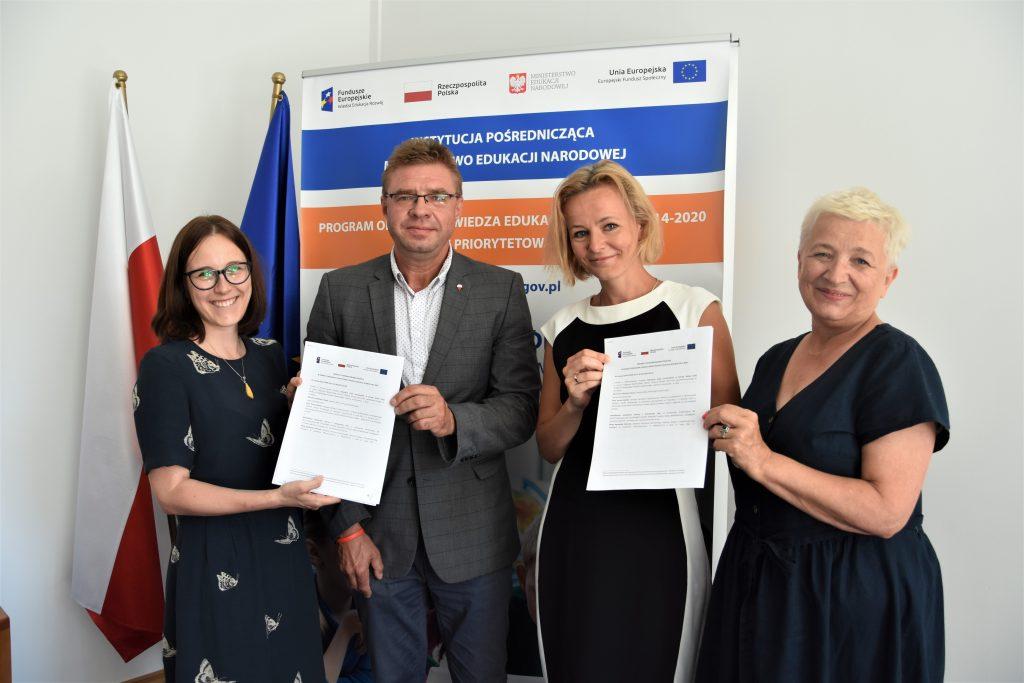 Podpisanie umowy - 4 osoby stoją i trzymają podpisane dokumenty