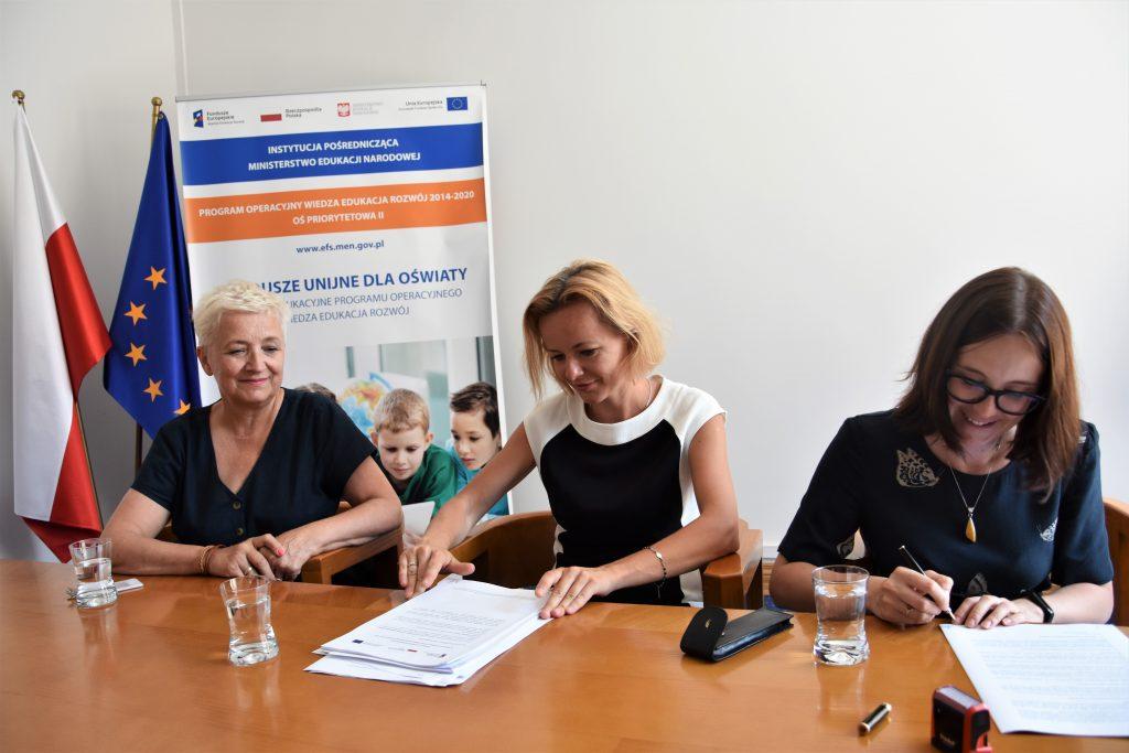 Podpisanie umowy - trzy osoby siedzą przy stole i podpisują dokumenty